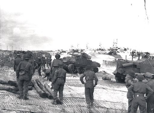 Des chars du 1st Hussars et des hommes de la 7e Brigade d'infanterie débarquent sur la plage encombrée à Courseulles-sur-Mer le 6 juin 1944.