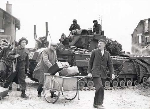 Avec l'aide d'un sergent, des civils français passent à côté d'un char à Bernières.