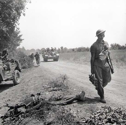 Troops of the Cape Breton Highlanders moving along a road near the Melfa river, May 24th, 1944. A dead German soldier lies by the roadside.