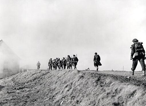 Infantry of the Chaudière Regiment going along dyke during the clearing of the flooded area near Cleve, Germany, February 10th, 1945.