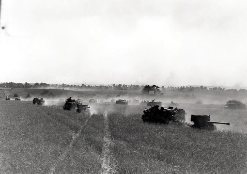 Vehicles from the 3rd Infantry Division moving through the countryside during Operation Tractable, August 14th, 1944. In the foreground, gunners towing 6-pounder antitank guns.
