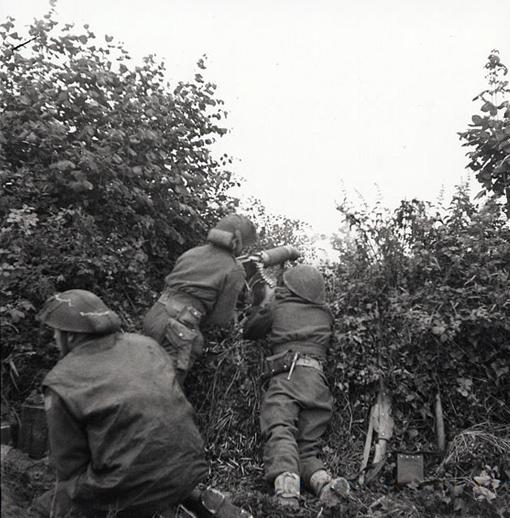 Cameron Highlanders of Ottawa machine gunners firing through a hedge during the attack on Carpiquet, July 4th, 1944.