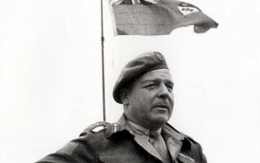 Le major-général R.F.L. Keller s'adresse aux troupes canadiennes en Normandie, le 2 août 1944. Le Red Ensign canadien flotte derrière lui.
