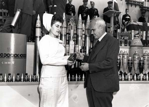Miss Edna Poirier presenting the Honourable C.D. Howe with the 100,000,000th 25-pounder shell produced in Canada. The ceremony took place at the Defence Industries Limited facility in Cherrier, Quebec, September 1944.