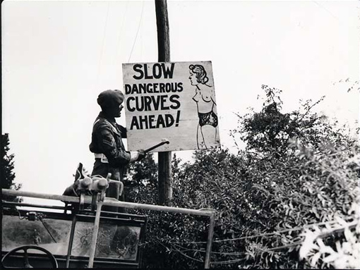 """Slow, Dangerous Curves Ahead"". Humour goes a long way when road signs must be read by young men – the majority of the Army. No. 2 Canadian Provost Company Corporal Ernie Nault of Meadow Lake, Saskatchewan, puts up sign along the road to Falaise, Normandy, 13 or 14 August 1944."