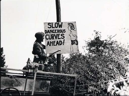« Lentement, courbes dangereuses en avant ». Rien de tel qu'un peu d'humour pour s'assurer que les jeunes hommes qui composent la majorité de l'Armée lisent les panneaux routiers. Le caporal Ernie Nault, de Meadow Lake (Saskatchewan), membre de la 2e Compagnie du Corps canadien de la prévôté, place un panneau de signalisation sur la route de Falaise (Normandie) le 13 ou le 14 août 1944.