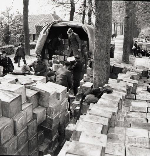 Dutch civilians loading a Canadian-supplied truck with food, following agreement amongst Germans, Dutch and Allies about the distribution of food to the Dutch population. Near Wageningen, Netherlands, 3 May 1945.