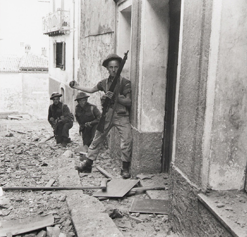 Three men of the Canadian Infantry Brigade preparing to send a hand grenade into a sniper's hideout in the Maltese Mountains, Campochiaro, Italy, 23 October 1943.