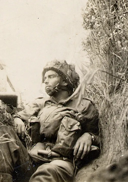 A weary paratrooper takes some rest in a slit trench. Varaville June 6, 1944.