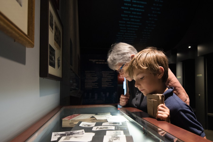 Colour Photo. A woman and young boy look at personal artifacts in a display case.