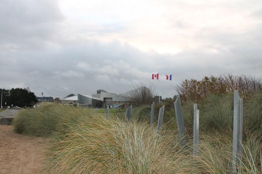 Colour photo. The Juno Beach Centre is visible through beach growth.