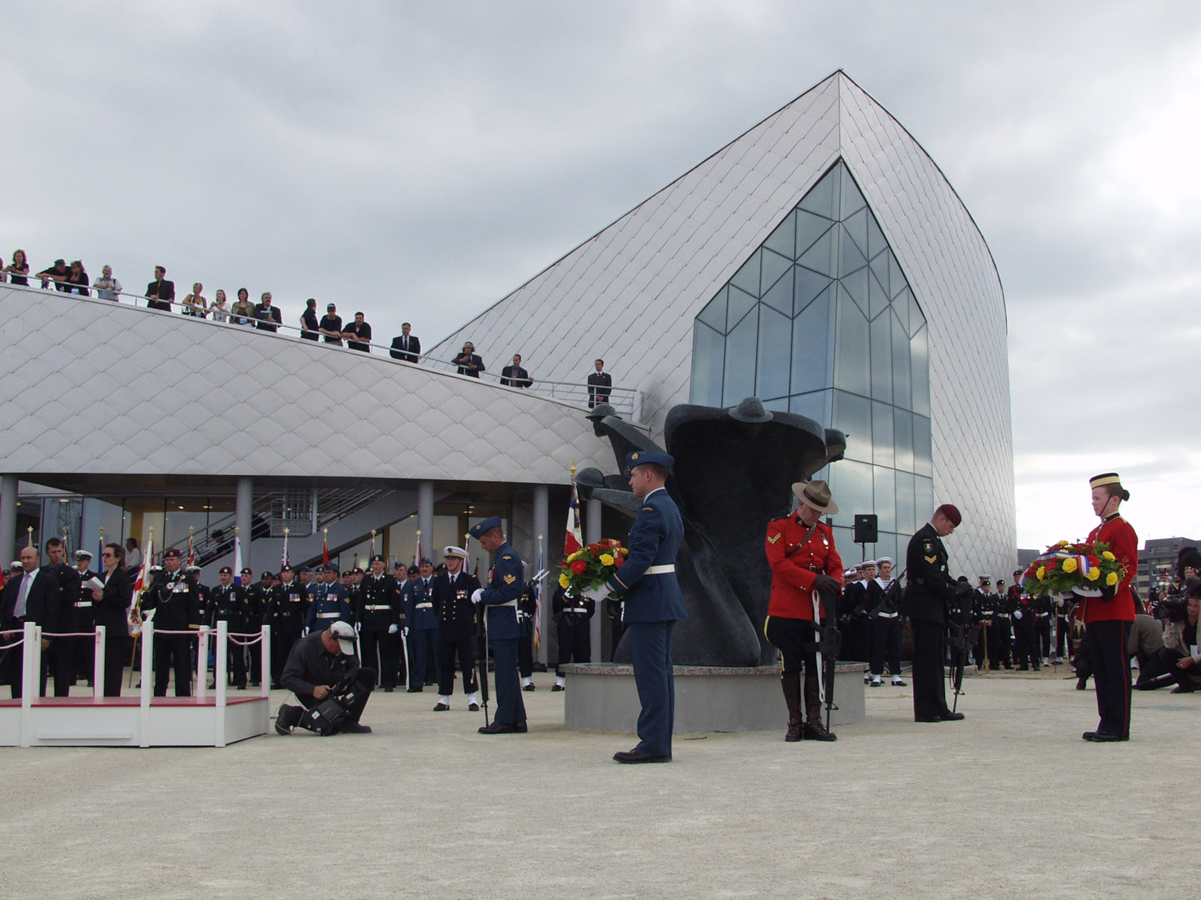Colour photo. People in uniform stand at attention in front of the Juno Beach Centre.