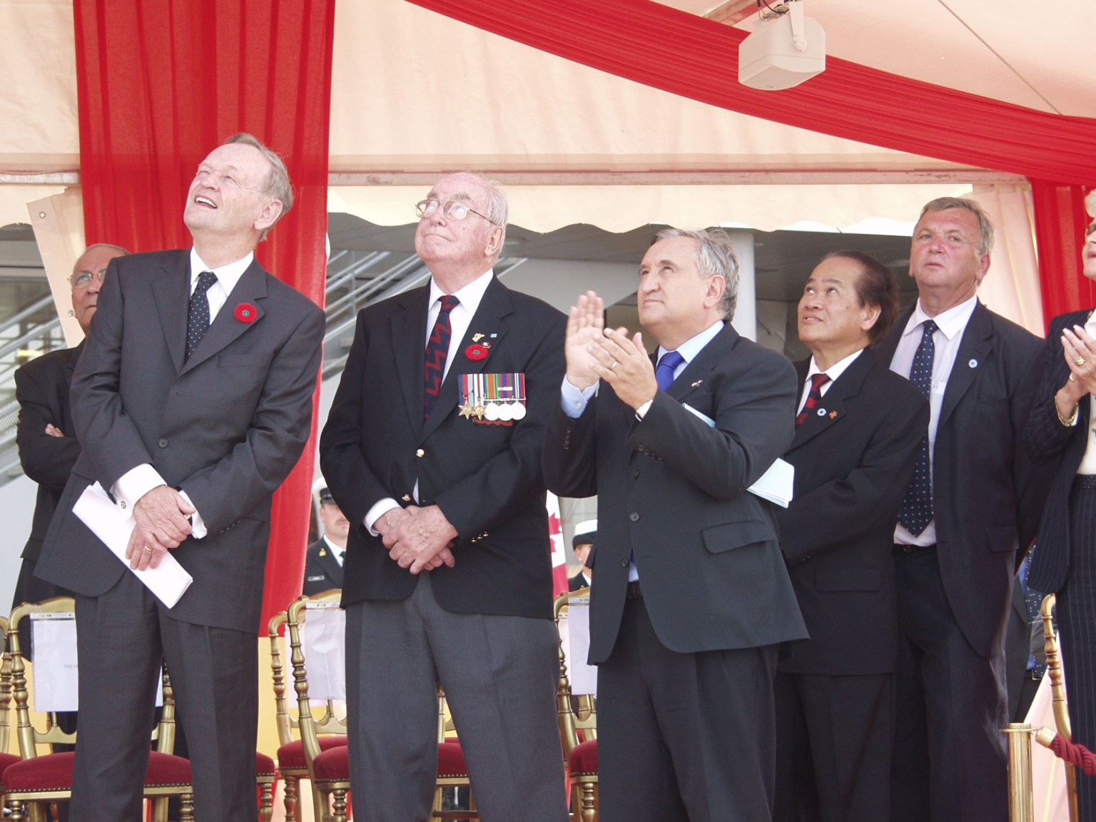 Colour photo. A group of men in suits look upwards.