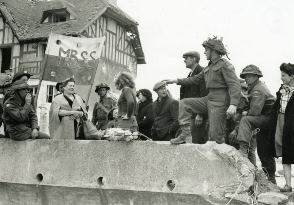 Black and white photograph.  Infantrymen of Le Régiment de la Chaudière talking with French civilians, Bernières-sur-Mer, France, 6 June 1944. Source: Lieut. Frank L. Dubervill / Canada. Dept. of National Defence / Library and Archives Canada / PA-132463 / Courtesy of the Juno Beach Centre Association