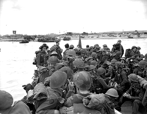 """Black and white photograph. Personnel of Royal Canadian Navy Beach Commando """"W"""" landing on Mike Beach, Juno sector of the Normandy beachhead, France, 8 July 1944.  Source: Lt Richard Graham Arless / Canada. Dept. of National Defence / Library and Archives Canada / PA-182953 / Courtesy of the Juno Beach Centre Association"""