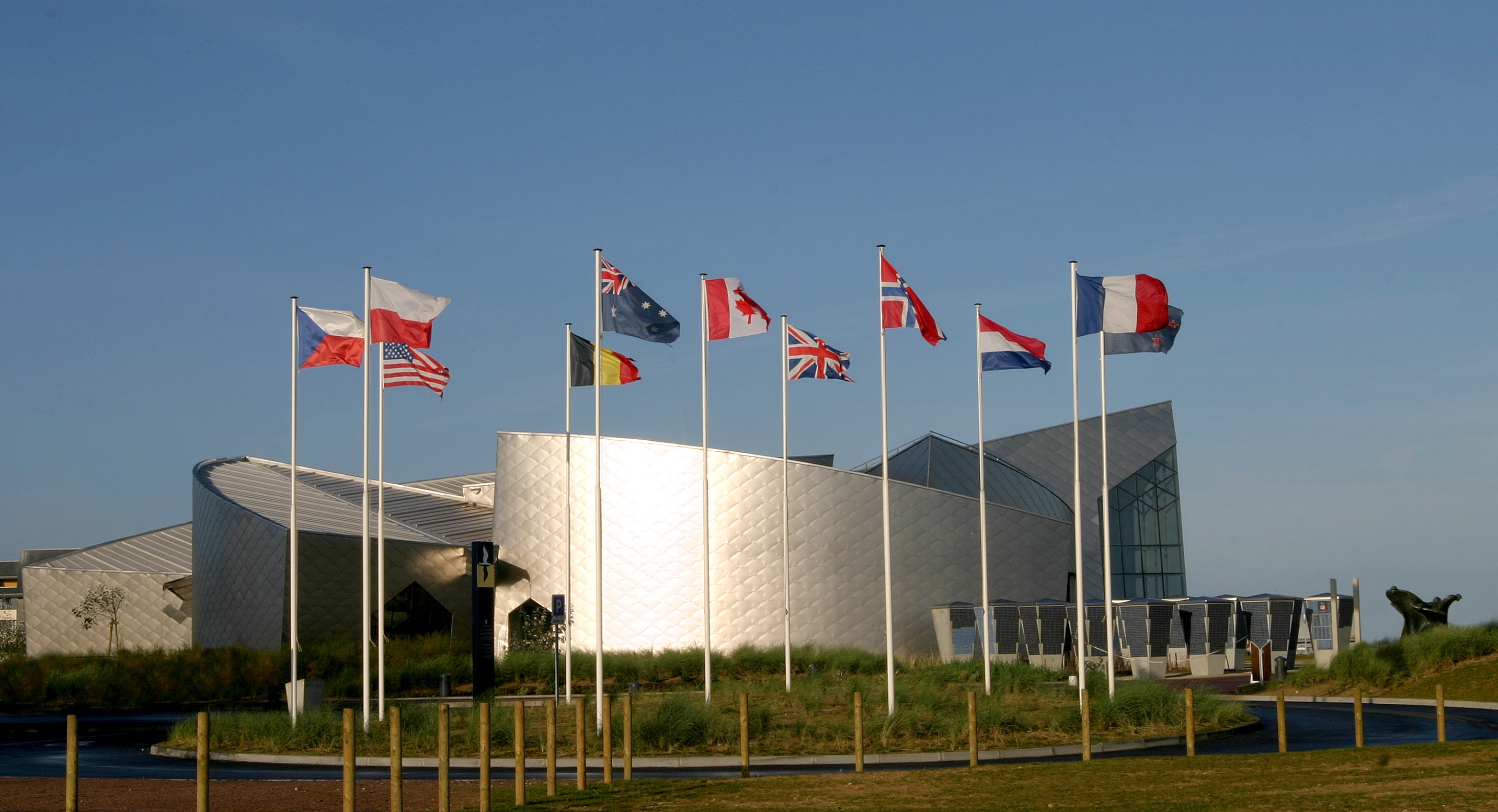 Colour photo. Juno Beach Centre viewed through 11 national flags.