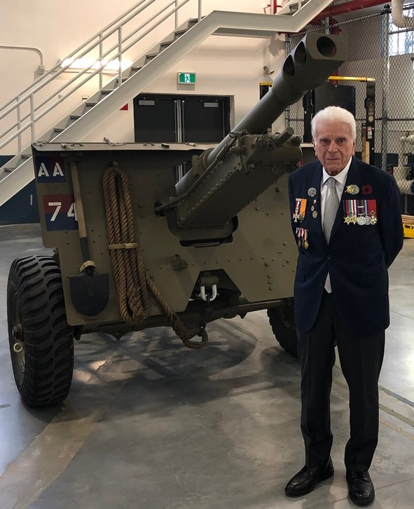 Norm Kirby poses with a 25-pounder gun in 2020.