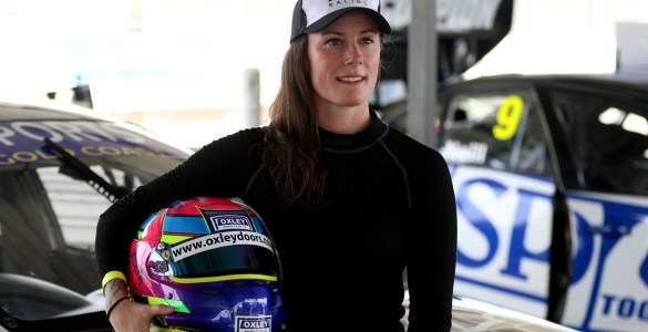 Abbie Eaton stood in front of car, helmet under arm