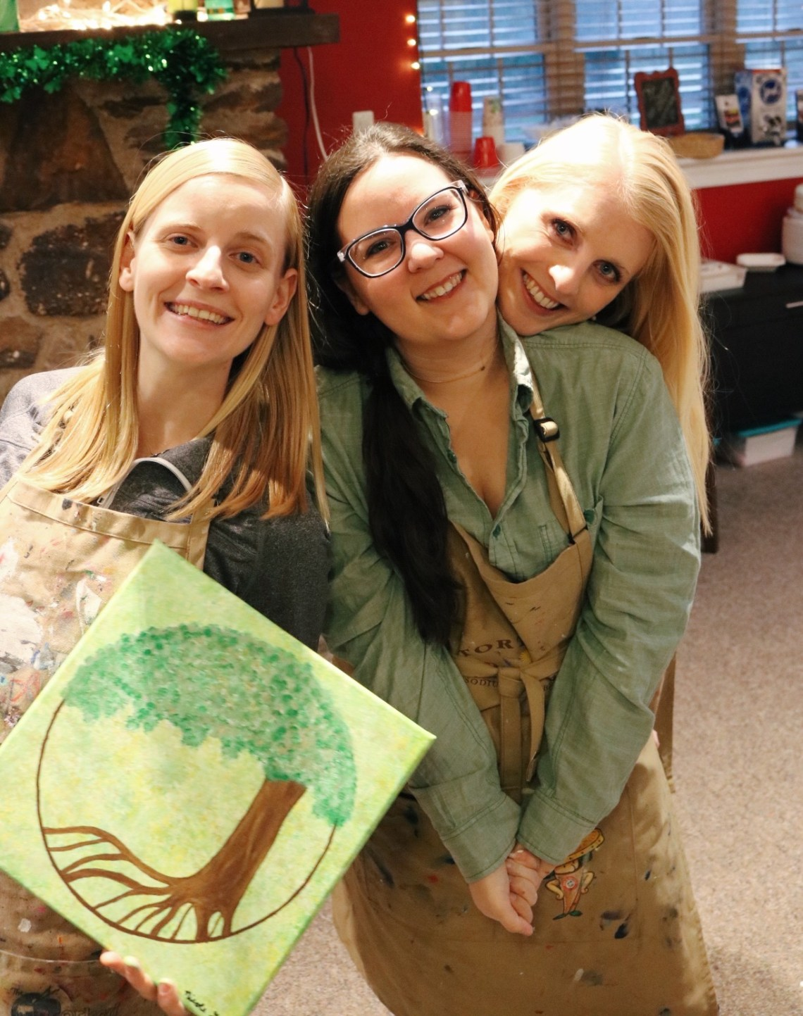 Me with my two friends smiling while my friend on the left holds up her finished tree of life painting