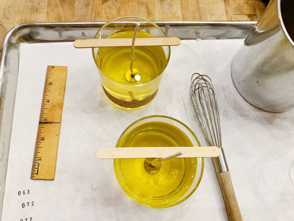 a photo of the candle making process. two glass candles with the oil filled in them but not hardened to wax yet