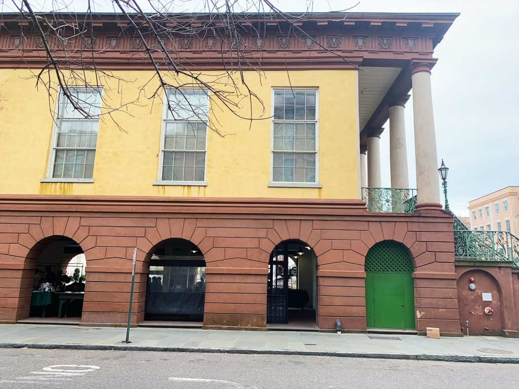a photo of the city market of charleston. it is a brick building with arched openings on the first level and a yellow outside on the second layer