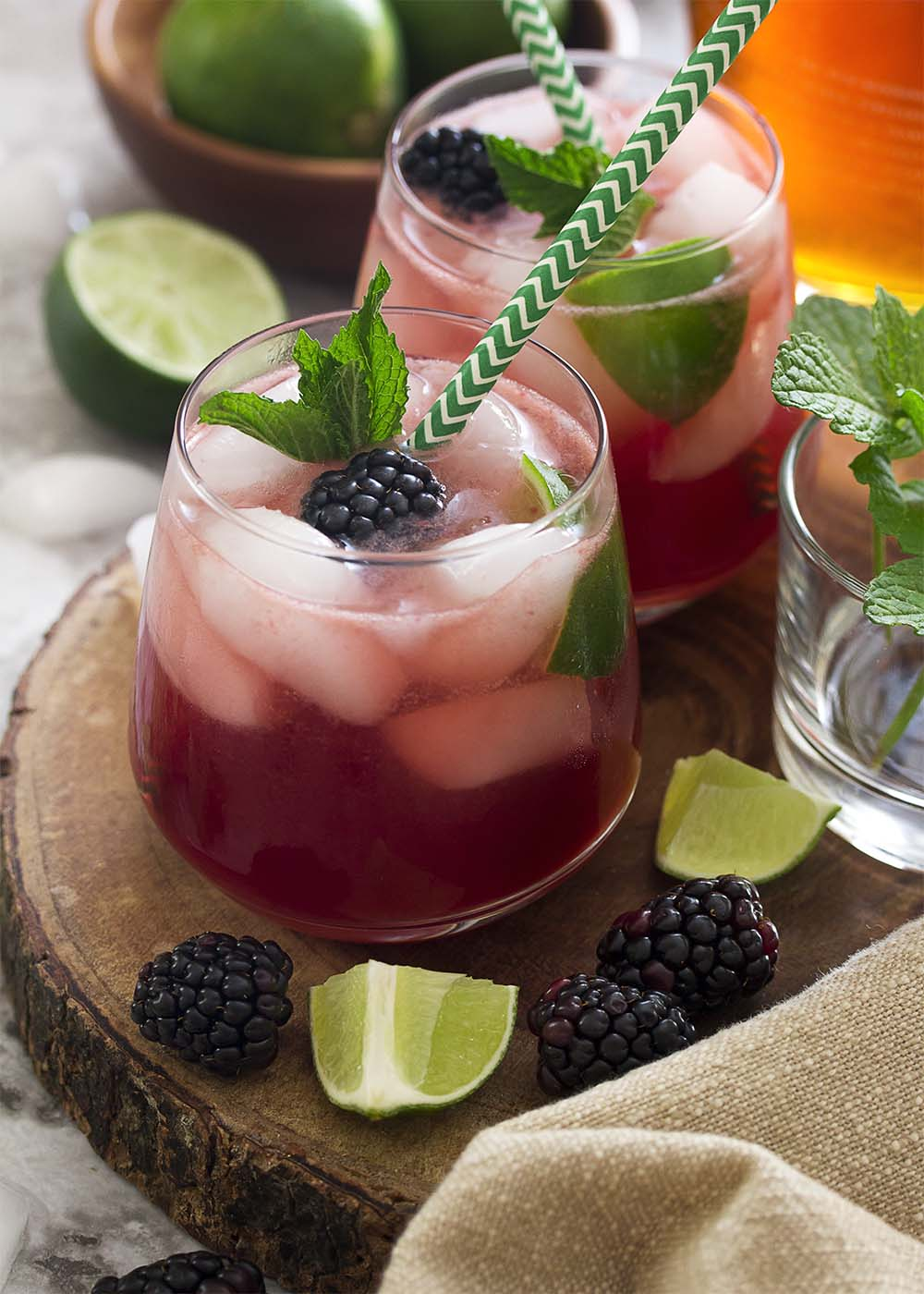 Two blackberry mojitos on a wooden tray and garnished with blackberries, lime, and mint.