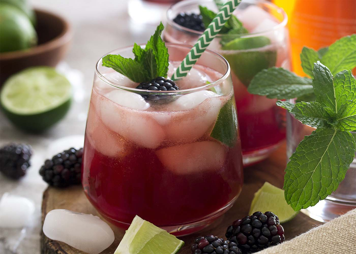 Side view of a blackberry mojito with a straw in the glass. Blackberries and lime scattered about.