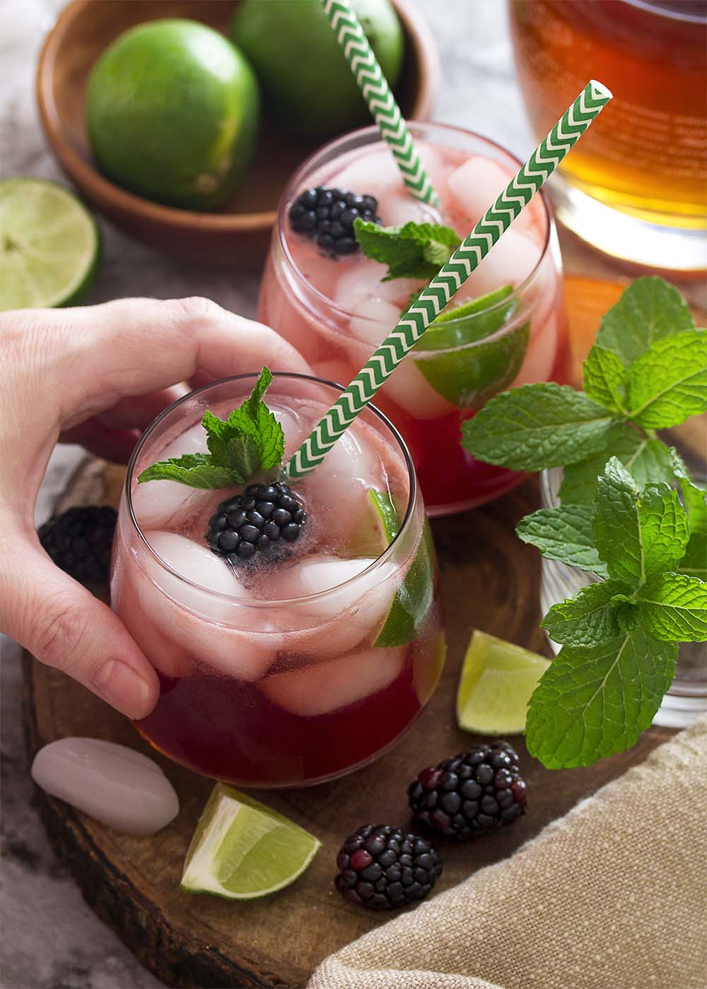 Top view of a hand reaching for a blackberry mojito.