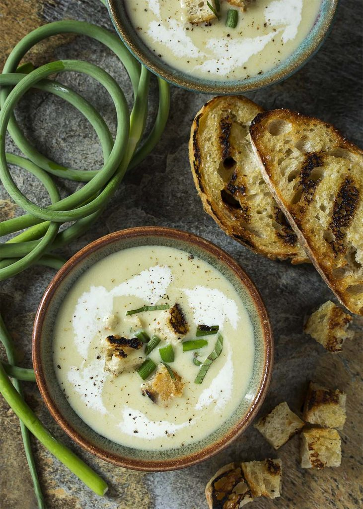 Wondering how to use garlic scapes? A great way to use them is to make a cold garlic scape soup! Perfect for summer and easy to make ahead. Scapes and leeks sauteed in butter and simmered with potatoes make a great twist on the classic French vichyssoise.