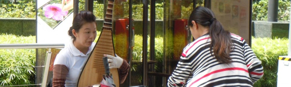 She is playing an instrument like a lute.I think it is called a pipa.