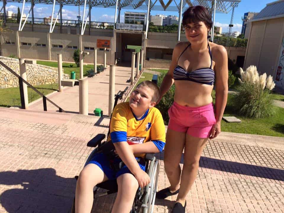 Jen standing in a bikini top and shorts with Ben in a wheelchair wearing a Mansfield Town football shirt both smiling in the sun.