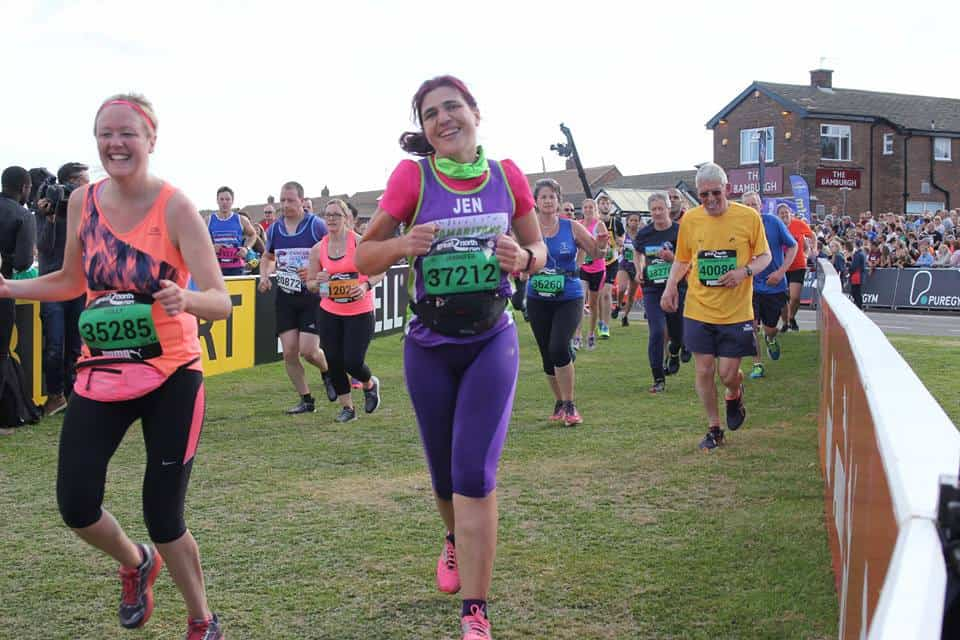 Jen running on grass with other runners in shot. Jen is wearing a Samaritans top and purple capris smiling and running with race number on