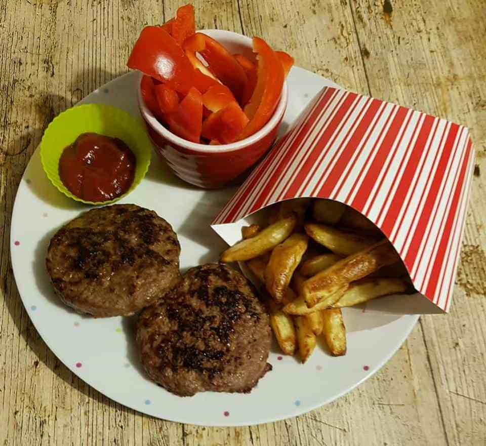 a large plate with 2 burgers, chips in a cardboard carton similar to a mcdonalds one, peppers in a large ramekin and a small pot with ketchup in