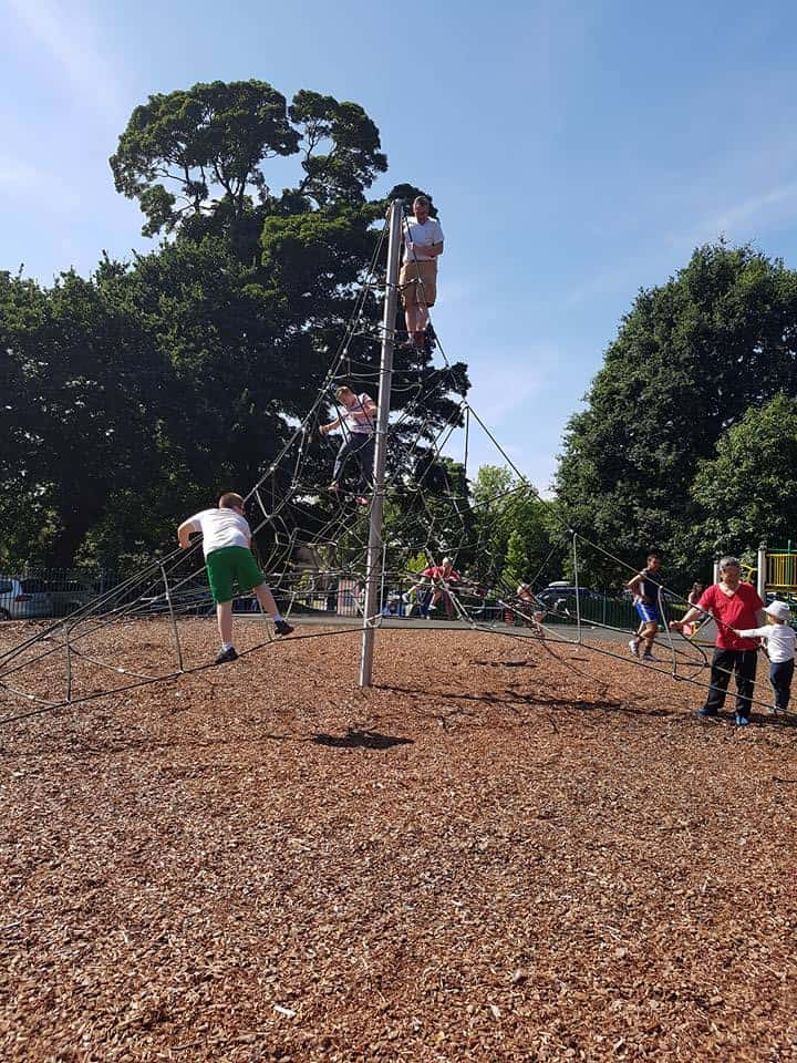 Children and adult climbing a pyramid rope climbing frame