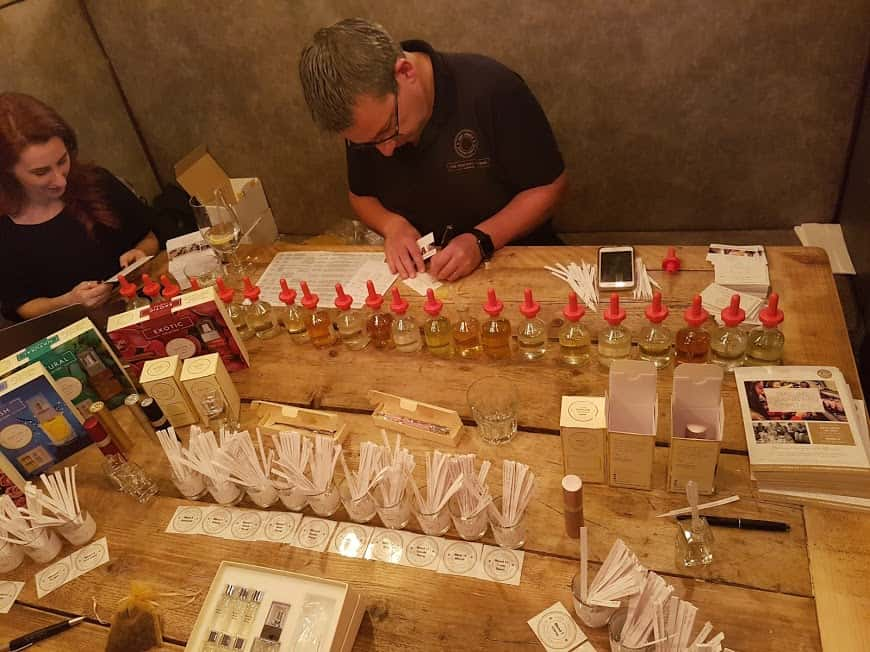 Two people making perfumes with lots of little bottles and droppers.