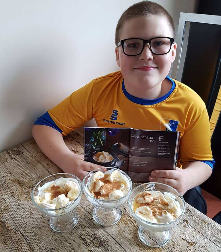 Ben showing recipe and pots of banana desserts