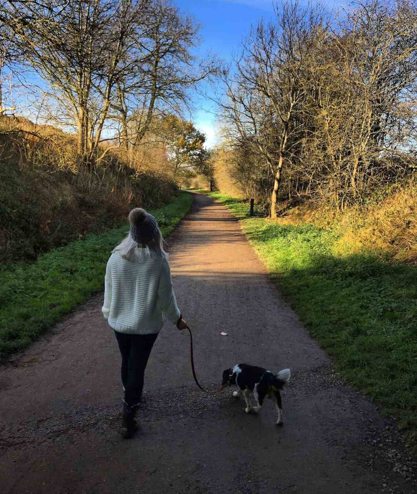 Lady walking a dog along a path in wooly hat and jumper
