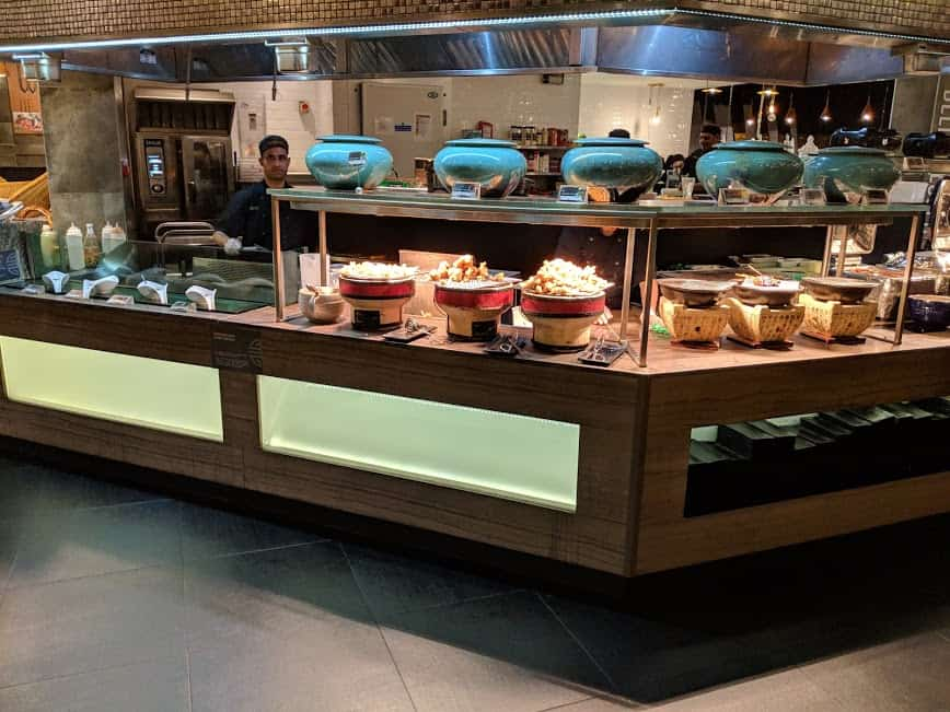 photo showing lots of serving bowls in the buffet full of foos and staff cooking in background