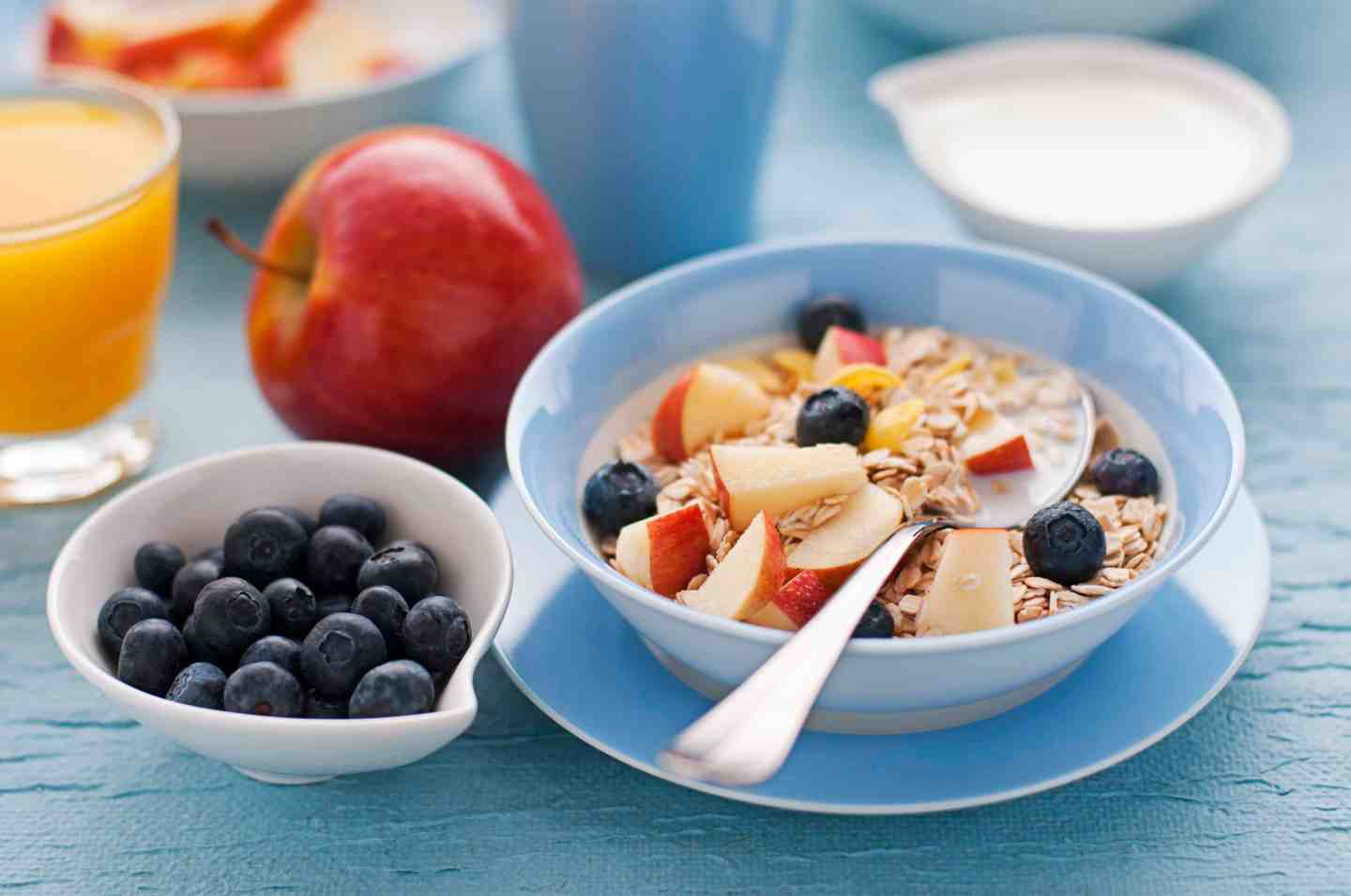 healthy breakfast of apple, blueberries and a bowl of muesli with both in on a table