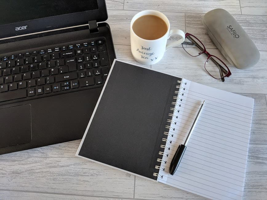 laptop, coffee, glasses, and notepad with pen on white wooden table top