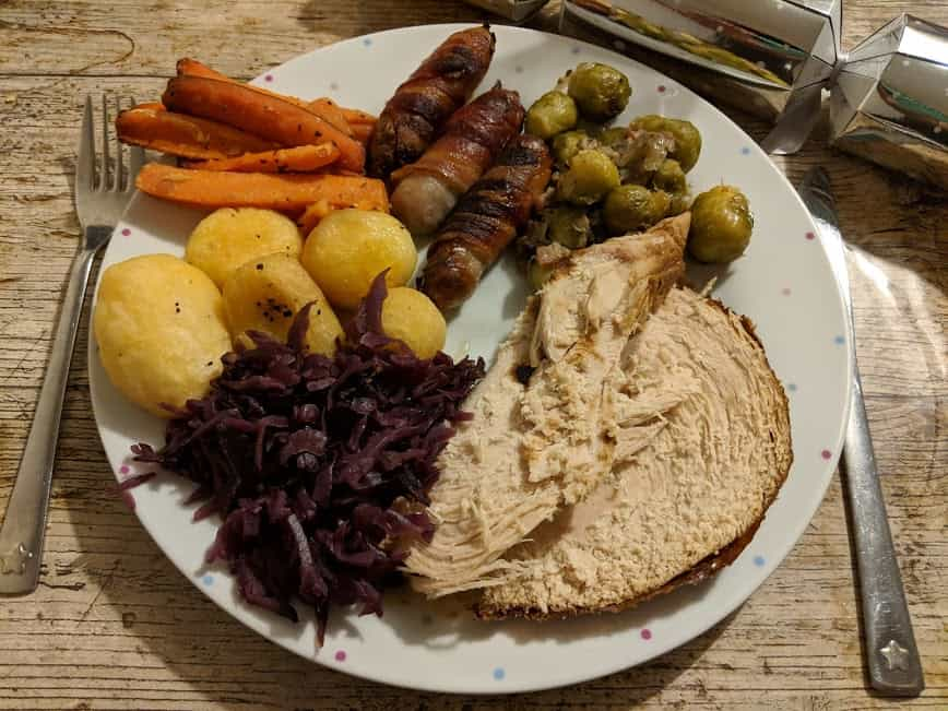 Plate of a turket roast dinner including potatoes, red cabbage, sprouts and carrots