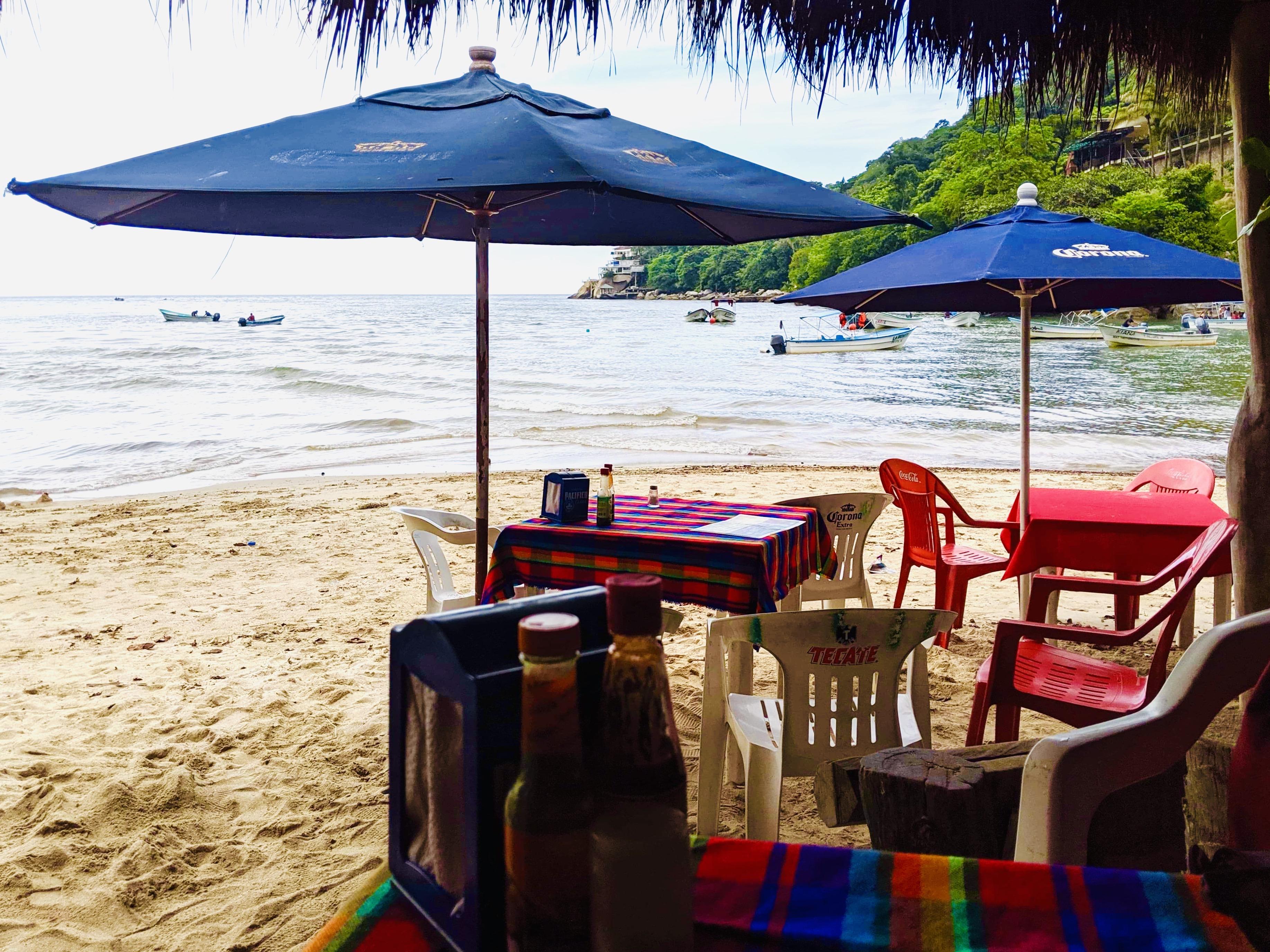 Beach side restaurant tables, with the beach of Boca de Tomatlan