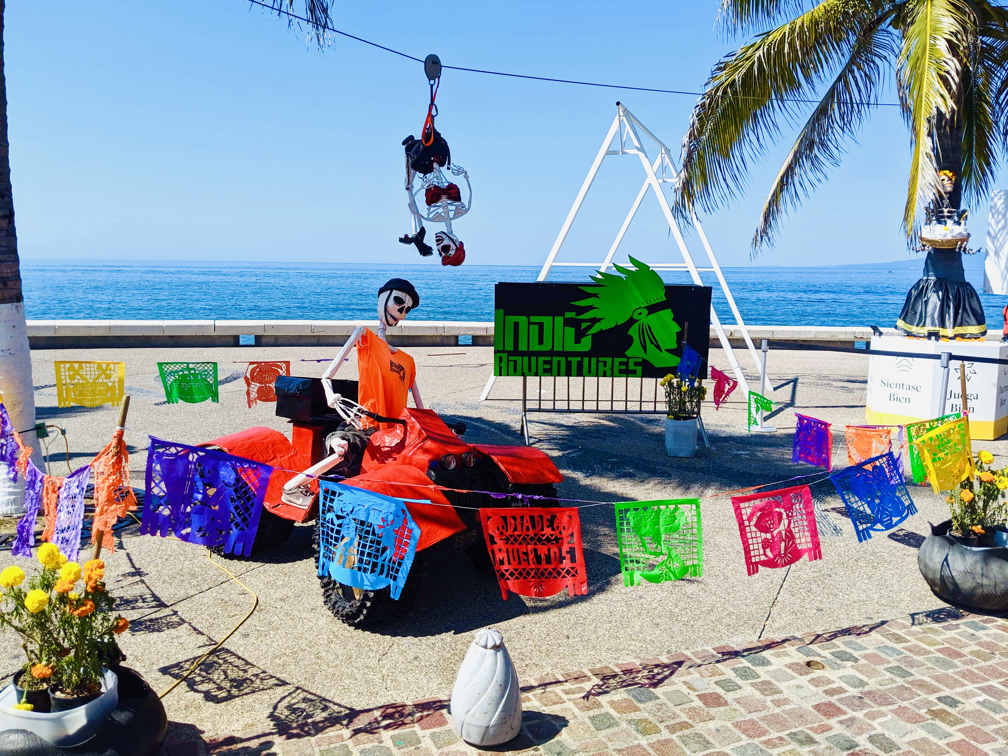 Day of the Dead skeleton dressed up on an atv on Malecon, with ocean in background
