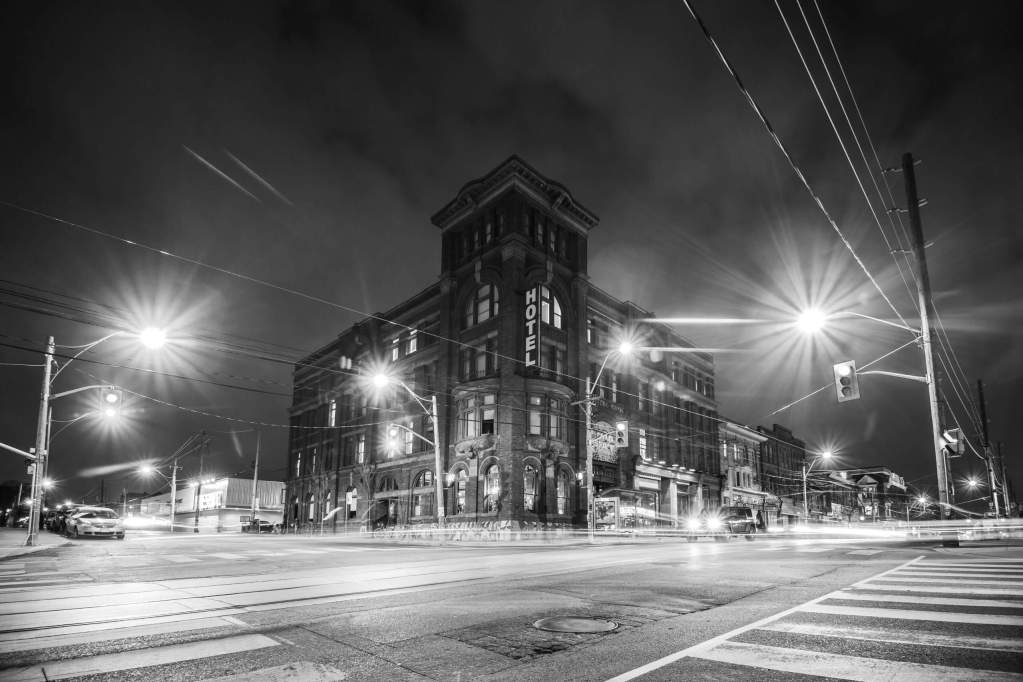 Black and white photo of a hotel on a street corner