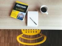 Stock photo showing a desk with cup of coffee, notepad, and German for dummies on it