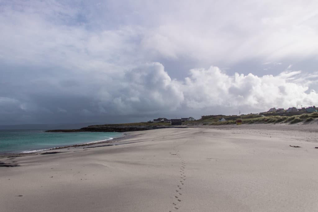 white sand beach next to the pier on inisheer