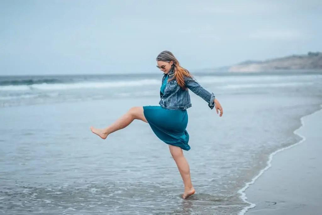 girl kicking leg on beach