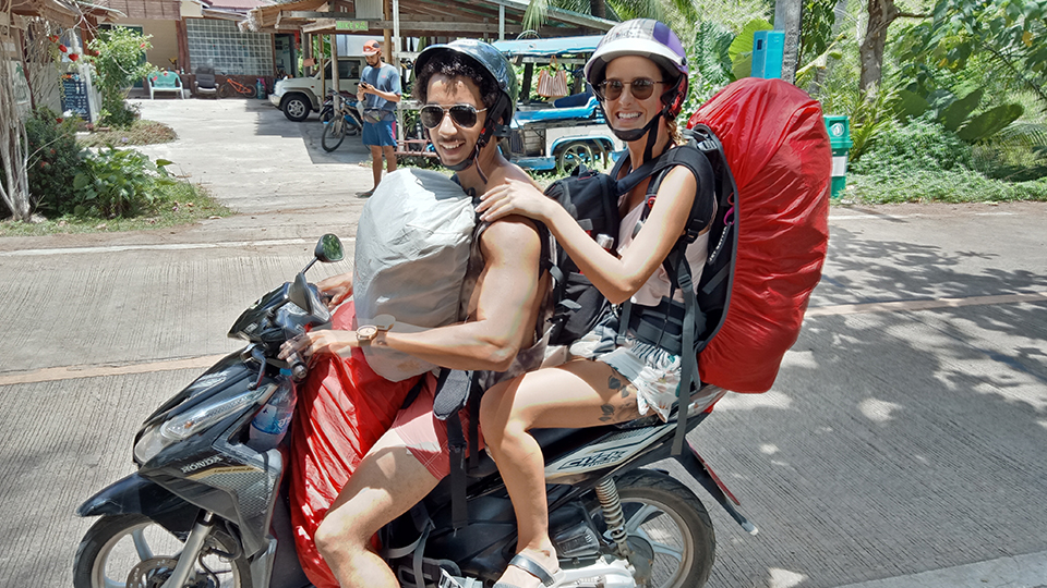 couple with backpacks on a scooter in thailand