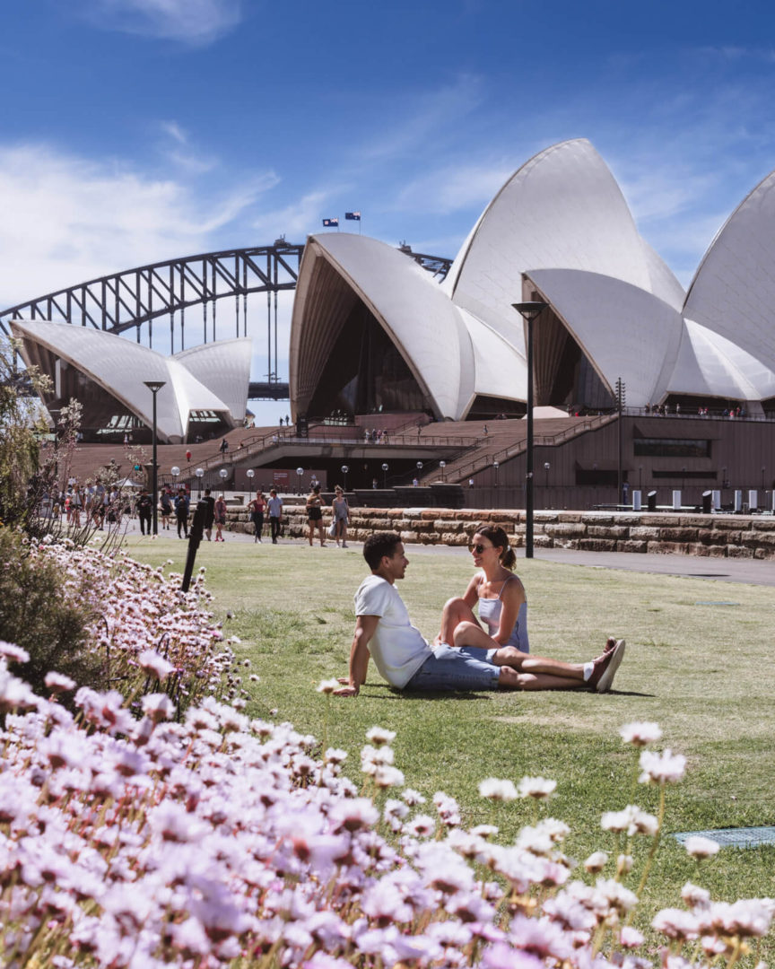 Couple relaxing outside sydney opera house with pink flowers