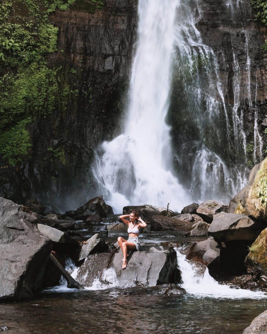 Gitgit Waterfall with girl sitting on a rock alone at the bottom of the waterfall in Bali